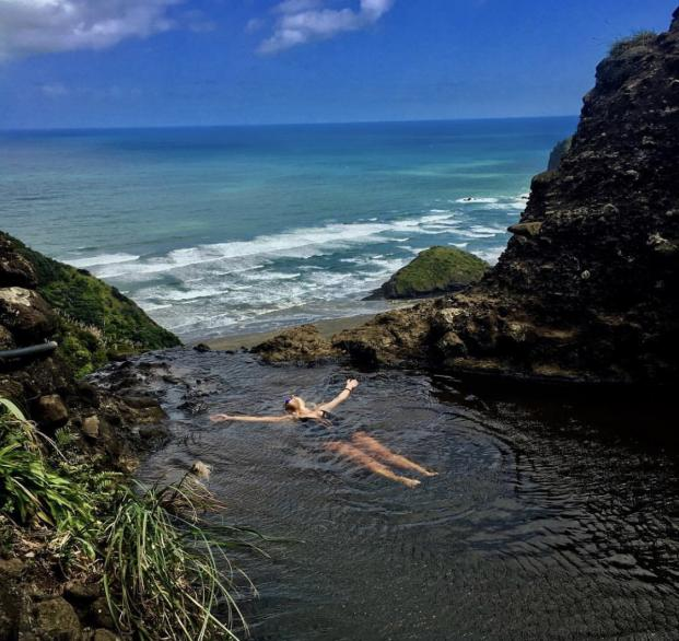 Danielle floats in a rock pool above a New Zealand beach