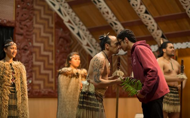 An international student experiencing a hongi greeting inside a marae in New Zealand