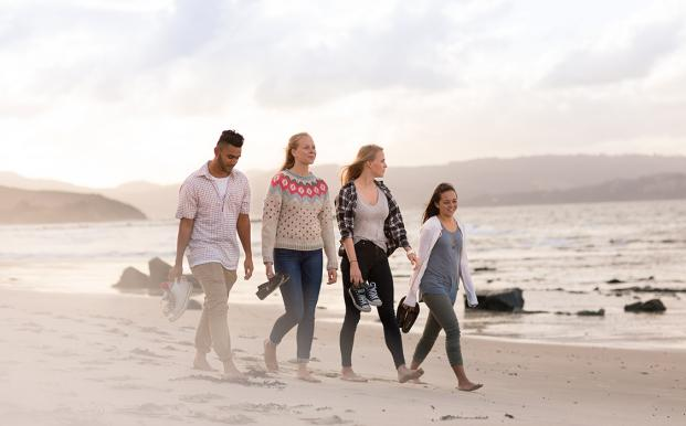 A group of international students walk along a beach in New Zealand