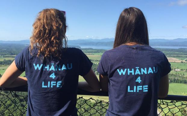 "North American Whānau Council Co-Presidents Sonia Richmond and Monica Petzold stand with their backs to the camera wearing tshirts that say ""whanau 4 life"""
