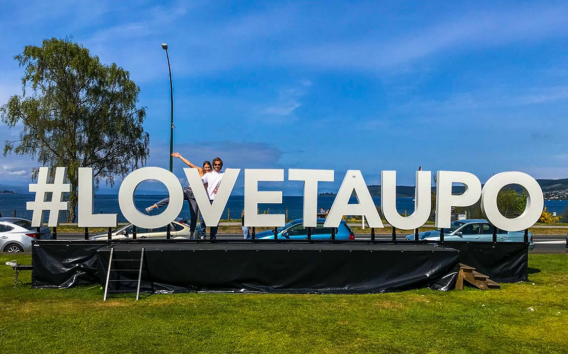 Ryan and Grace pose by a #LoveTaupo sign