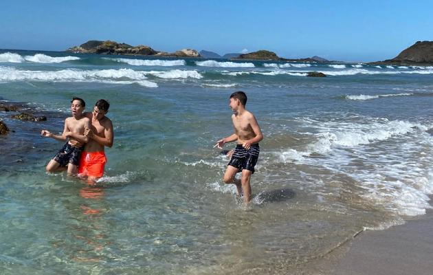 Students at the beach playing in the sea