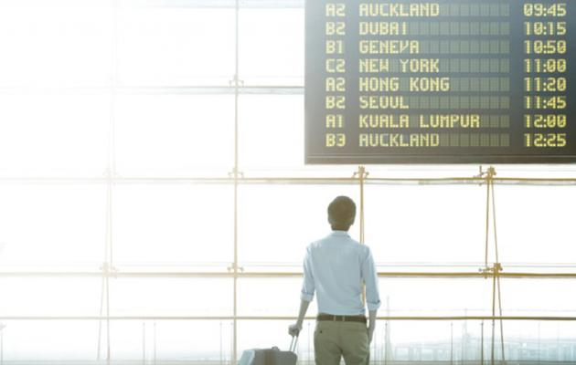 Student at airport looks up at departures board