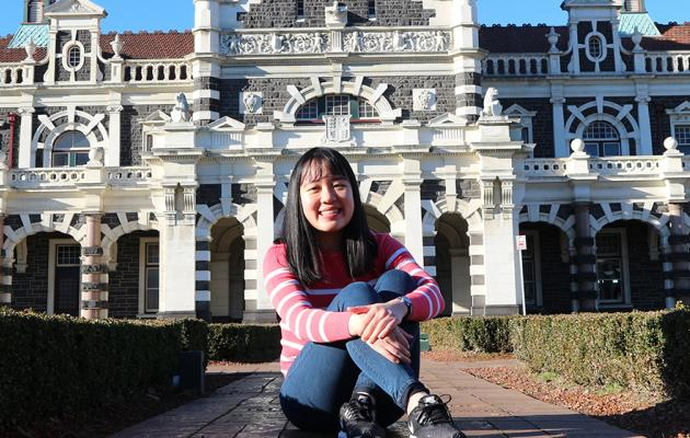 Chui San Sung sits in front of one of the University of Otago's iconic buildings