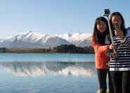 Chinese students on shores of Lake Tekapo taking selfie